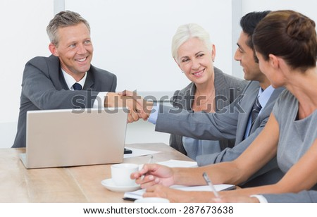 Executives shaking hands in board room meeting at office - stock photo