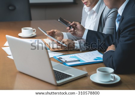 Executives using various devices at the meeting: technology in business