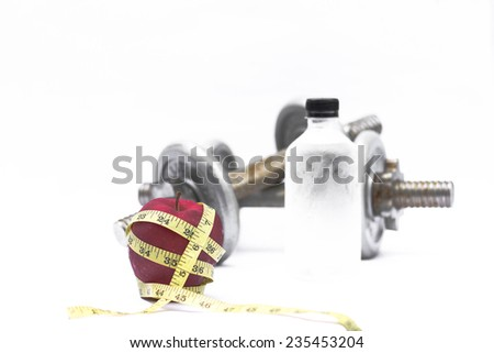 Exercise and healthy diet concept with dumbbells, red apple, measuring tape and bottle of water. - stock photo