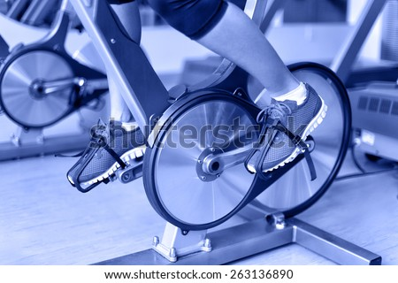 Exercise bike with spinning wheels. Woman excising biking in fitness center. closeup of pedals. Professional fitness center equipment. - stock photo