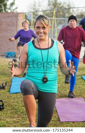 Exercise instructor leading adults in fitness outdoors