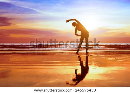 exercise on the beach at sunset, beautiful silhouette of young woman - stock photo