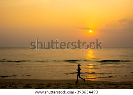 Exercise runner on the beach have sea sunset background. silhouette style - stock photo