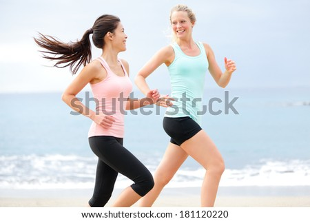 Exercise running women jogging happy on beach training as part of healthy lifestyle. Two fit female runners talking happy and smiling during workout. Multiracial Asian and Caucasian woman. - stock photo