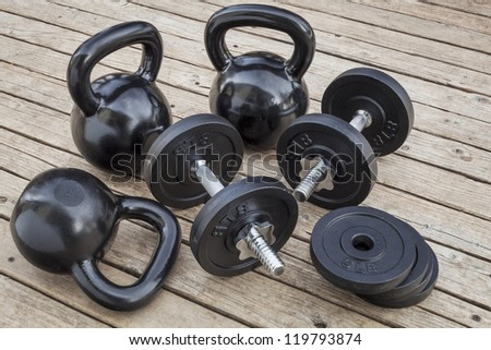 exercise weights - kettlebells and dumbbells on a wooden deck - a home gym concept - stock photo