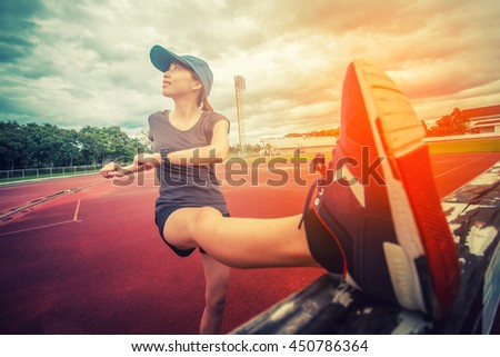 Exercise woman stretching hamstring leg muscles during outdoor running workout. Smiling happy mixed race Asian / Caucasian sport fitness model in Stadium - stock photo
