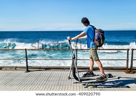 Exercises everyday outdoor. Young sporty, active boy (teenager) working (doing) exercises on equipment and having fun, enjoying ocean. Outside. Copy space. Empty place for you message.  - stock photo