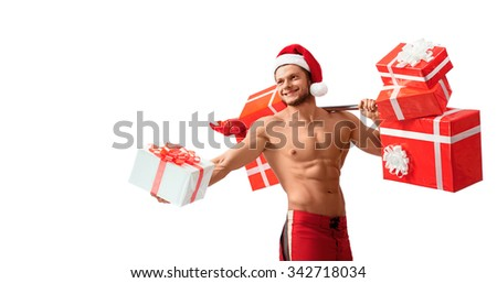 Exercises for everyone. Super fit and strong Santa Claus holding out a gift with a barbell full of presents in his other hand copyplace on the side - stock photo