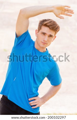Exercising outdoors. Handsome young man doing stretching exercises while standing outdoors