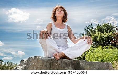 exercising outside - radiant 50s yoga woman sitting on a stone, seeking for spiritual balance with tree background,low angle view - stock photo