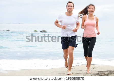 Exercising running couple jogging on beach. Runners training on sand by the ocean smiling happy in full body length. Interracial fit fitness couple, Asian woman and Caucasian man runner. - stock photo