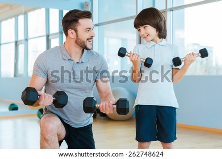 Exercising together. Happy father and son exercising with dumbbells and smiling while standing in health club  - stock photo
