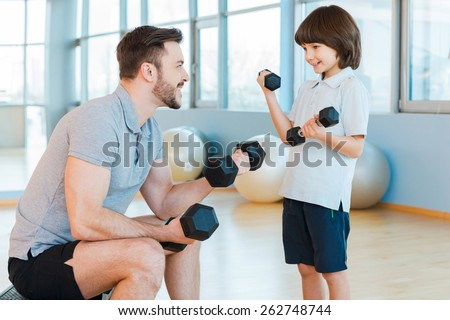 Exercising together is fun. Happy father and son exercising with dumbbells and smiling while both standing in health club  - stock photo