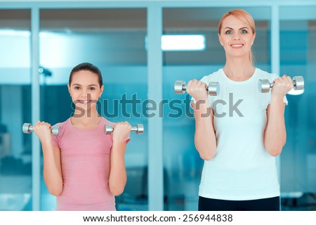 Exercising with dumbbells. Beautiful mature woman and her teenage daughter in sports clothing exercising with dumbbells and smiling while standing against glass wall in the gym - stock photo