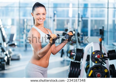 Exercising with dumbbells. Happy young woman exercising with dumbbells and smiling while standing in gym - stock photo