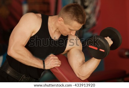 exercising with dumbbells.man with weight training equipment on sport gym club. Blurred background.