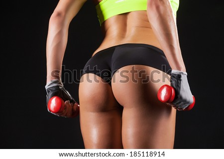 Exercising with dumbbells. Rearview of an attractive young woman holding dumbbells - stock photo
