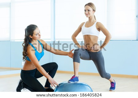 Exercising with fitness ball. Beautiful young woman in sports clothing exercising with personal trainer - stock photo