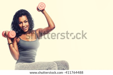 Exercising with fitness ball. Side view of wooman sitting on fitness ball and doing exercises with dumbells.