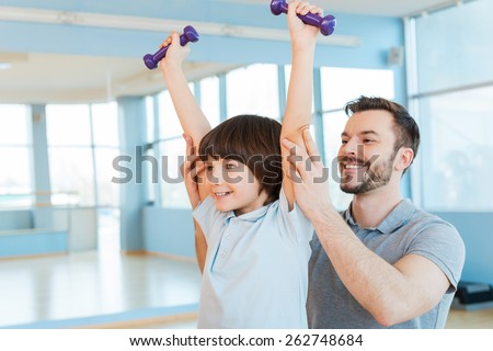 Exercising with fun. Happy father supporting his son in weight training while both standing in health club  - stock photo