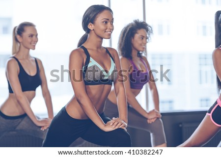 Exercising with joy. Close-up of beautiful young women with perfect bodies in sportswear exercising with smile while standing in front of window at gym