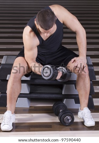 Exercising with weights while sitting on stepper in the gym - stock photo