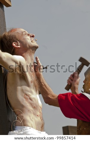 EXETER - APRIL 6: Jesus's hands are nailed to the cross as part of the crucifixion reenactment during the Good Friday Walk of Witness in Exeter City Centre on April 6, 2012 in Exeter, UK
