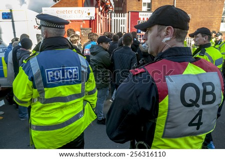 EXETER, ENGLAND - FEBRUARY 21, 2015: Devon and Cornwall Police watch Plymouth  football fans during the police operation at the League 2 football match between Exeter City FC and Plymouth Argyle FC  - stock photo