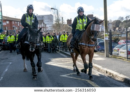 EXETER, ENGLAND - FEBRUARY 21, 2015: Police horses escort Plymouth Argyle football fans during the police operation at the League 2 football match between Exeter City FC and Plymouth Argyle FC