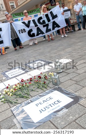 EXETER, ENGLAND - JULY 15, 2014: Peace signs, flowers and some of the peace campaigners during the Peace Vigil for Gaza in Exeter's Princesshay Square. - stock photo