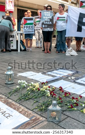 EXETER, ENGLAND - JULY 15, 2014: Peace signs, flowers with peace campaigners in the background during the Peace Vigil for Gaza in Exeter's Princesshay Square. - stock photo