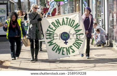 EXETER, ENGLAND - MARCH 7, 2015: International Women's Day banner leads the march during the Walk for Peace through the city of Exeter to celebrate International Women's Day.