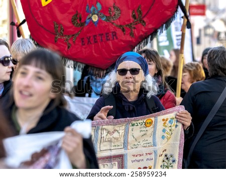 EXETER, ENGLAND - MARCH 7, 2015: Women wearing dark glasses and holding a banner during the Walk for Peace through the city of Exeter to celebrate International Women'??s Day. - stock photo