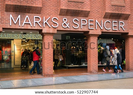 Exeter, England, UK - 22 November 2016: Unidentified people walk by Marks & Spencer store on High Street. The British brand announced closure of 60 clothing and home stores so it can focus on food.