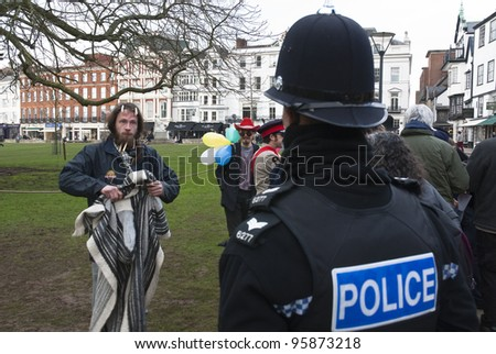 EXETER - FEBRUARY 11: A Devon & Corwall policeman has a discussion with Occupy Exeter activist dropping rubbish during Occupy Exeter's leaving the green in Exeter  on February 11, 2012 in Exeter, UK - stock photo