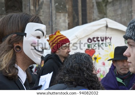 EXETER - JANUARY 28: An Occupy Exeter activist wearing a Guy Fawkes mask before the movements direct action against the Exeter branches of Topshop, HSBC & Vodaphone   on January 28, 2012 in Exeter, UK - stock photo