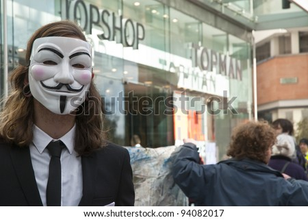 EXETER - JANUARY 28: An Occupy Exeter activist wearing a Guy Fawkes mask outside the Exeter branch of Topshop  on January 28, 2012 in Exeter, UK - stock photo