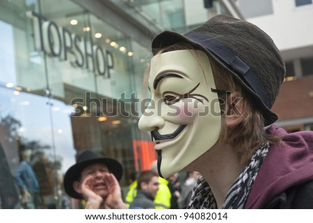 EXETER - JANUARY 28: An Occupy Exeter activist wearing a Guy Fawkes mask outside the Exeter branche of Topshop  on January 28, 2012 in Exeter, UK - stock photo