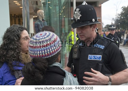 EXETER - JANUARY 28: Devon & Corwall police officers confronts two Occupy Exeter activists during their direct action outside the Exeter branch of Topshop  on January 28, 2012 in Exeter, UK - stock photo