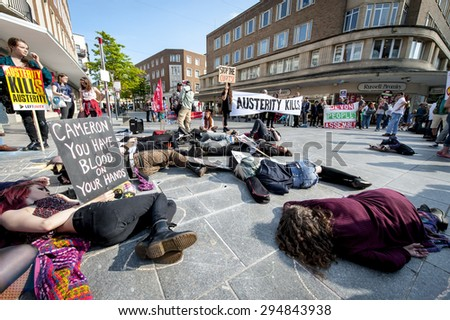 EXETER - JULY 8: Anti-austerity demonstrators play dead during the Exeter Budget Day Action #AusterityKills in Exeter City Centre on july 8th, 2015 in Bedford Square, Exeter, UK