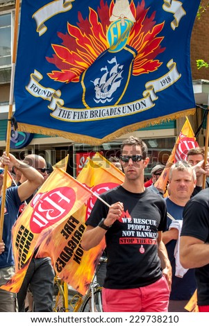 EXETER - JULY 10: Fire Brigade Union member walks along Exeter High Street during the public sector workers national day of action in Exeter City Centre on July 10,  2014 in Exeter, Devon, UK - stock photo
