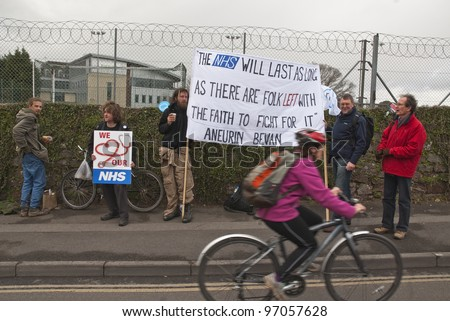 EXETER - MARCH 7:  A cyclist travels past a sign , during the NHS reform protest outside the Royal Devon & Exeter Hospital on March 7, 2012 in Exeter, UK - stock photo