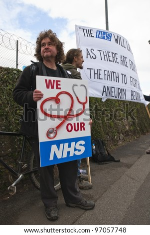 "EXETER - MARCH 7:  Activist Bruce Chapman holds a placard that says ""We Love our NHS"", during the NHS reform protest outside the Royal Devon & Exeter Hospital on March 7, 2012 in Exeter, UK - stock photo"