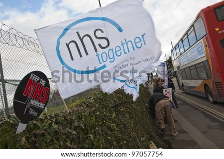 EXETER - MARCH 7:  An NHS Together flag flaps in the wind as a bus travels past, , during the NHS reform protest outside the Royal Devon & Exeter Hospital on March 7, 2012 in Exeter, UK - stock photo