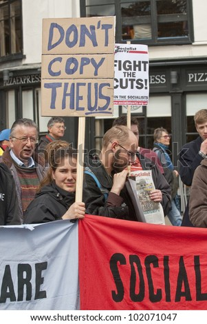 "EXETER - MAY 7: A protester holds a placard saying ""Don't Copy Theus"" at Exeter Cathedral Yard as part of the May Day rally against the coalition governments spending cuts on May 7, 2012 in Exeter, UK"