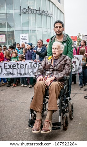 EXETER - NOVEMBER 16: Man in a wheel-chair is pushed along with the Exeter Together march during the Exeter Together march and diversity festival on November 16, 2013 in Exeter, Devon, UK - stock photo