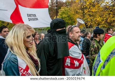 EXETER, UK - NOVEMBER 16: English Defence League member in a Burka and other EDL supporters march during the English Defence League march and rally November 16, 2013 in Exeter, Devon, UK - stock photo