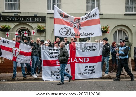 EXETER, UK - NOVEMBER 16: English Defence League supporters hold up flags will a man walks passed during the English Defence League march and rally November 16, 2013 in Exeter, Devon, UK - stock photo