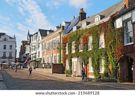 EXETER, UK - SEPTEMBER 12 2014: Pedestrians walk by businesses and residences on Cathedral Close and Cathedral Yard. This is a popular area for tourists and residents to relax near Exeter Cathedral. - stock photo