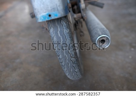 Exhaust of motorcycle and the wheel , from back angle.